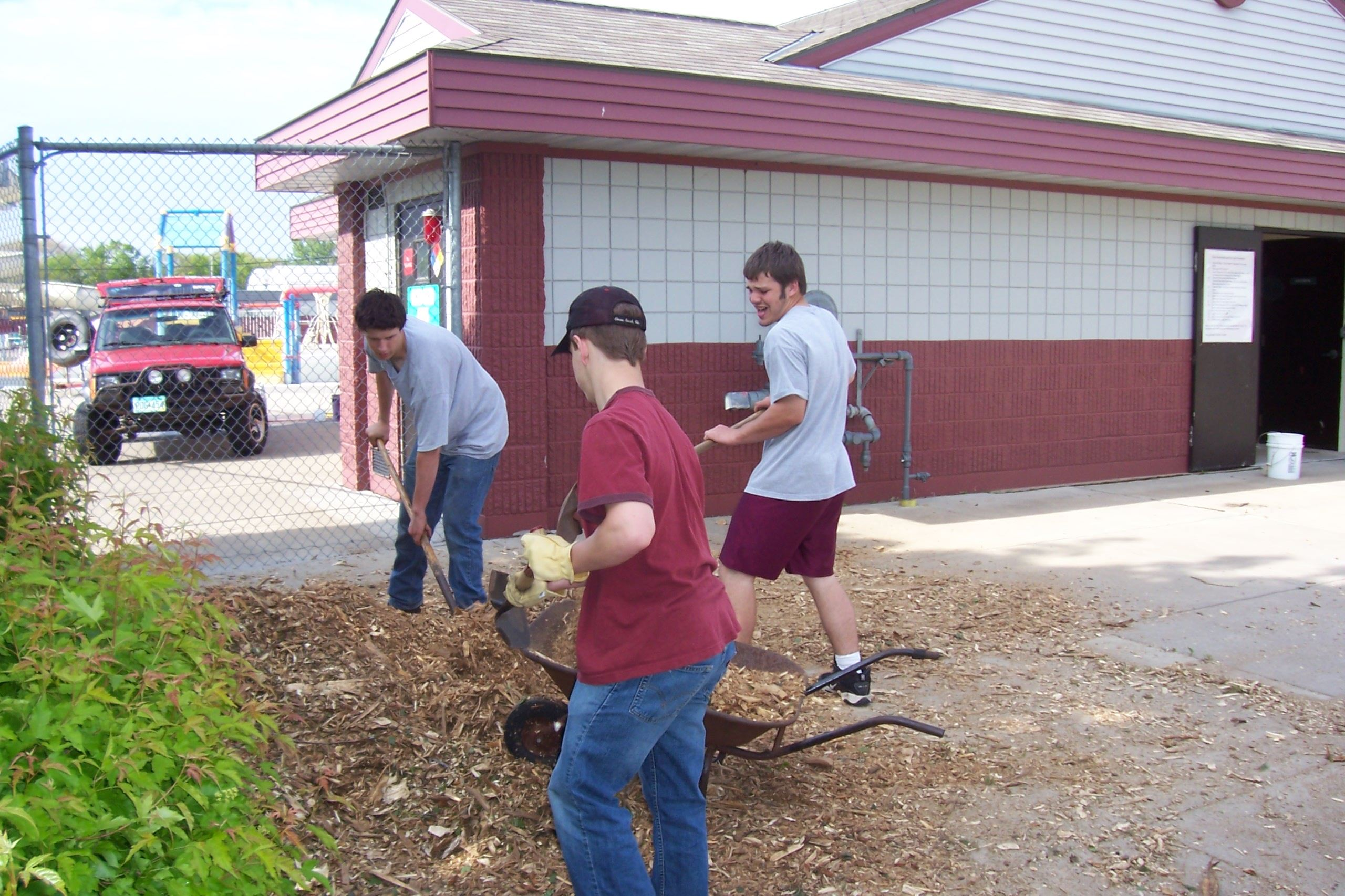 Anoka football players spreading wood chips in landscaping